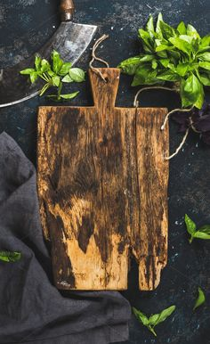 #Fresh green basil leaves  Fresh green basil leaves with herb chopper knife rustic cutting board in center over grunge dark blue plywood texture. Top view copy space vertical composition