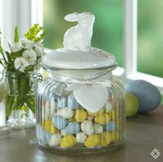 """Bunny Candy Dish - With its white ceramic bunny lid, this sparkling clear glass jar is a beautiful holder for candy or a few faux flowers! Comes with a white ribbon and attached heart at top of jar. 4-1/4"""" diameter and 6-1/2"""" high. ($9.99)"""