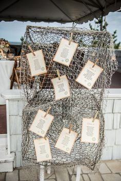 How unique is this reception seating display for a beach wedding? Cardstock clothespinned to a fishing net! {@dkpullen}