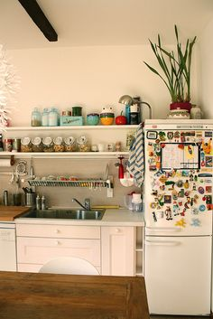 "I love how this kitchen feels ""real"" with the magnets on the fridge, dishtowels, etc yet still looks stylish. Love that above the sink drainage too."