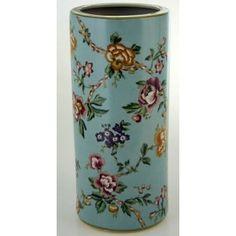 Paraguero cerámica Leslie con flores sobre fondo azulado.