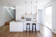 Kitchen: gloss white handleless cabinets, white stone benchtops, copper pendant lights, marble splashback, black bar stools, minimalist staircase