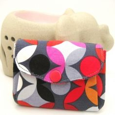This palm sized pouch has two flaps and three separate compartments to hold all manner of coins, cards and paper money.