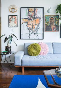 Sala de estar tem parede galeria, sofá cinza e almofadas redondas coloridas.