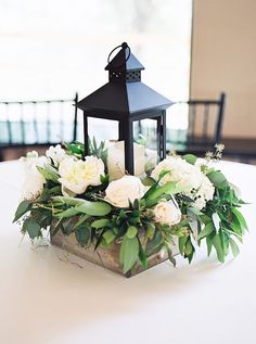 Place a candle in a lantern then place that in a wooden box with florals - so chic!