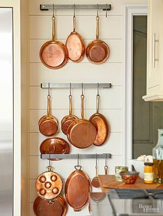Industrial stainless-steel racks hold a collection of vintage copper pots. The contemporary mix of metals elegantly contrasts with this kitchen's traditional-style wood-plank walls.