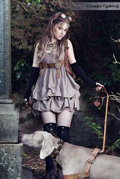 Steamgirl and Steampup - A sweet babydoll style dress with a brown leather harness (covered in gears), armwarmers, over the knee socks, statement necklace, goggle, and adorable dog in steampunk harness! - For costume tutorials, clothing guide, fashion inspiration photo gallery, calendar of Steampunk events, & more, visit SteampunkFashionGuide.com