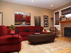 Lush red L-shaped sectional sofa wraps around this plush brown oval ottoman in fabric upholstery, with removable tray table on cushion surface.
