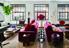 In the living room of Naomi Watts and Liev Schreiber's Ashe + Leandro–designed Manhattan apartment, a 19th-century Gabon mask from Throckmorton Fine Art and an artwork by Paul Morehouse overlook matching velvet-covered RH sofas, which are separated by a Ralph Lauren Home console. The cocktail table is by Robert Pluhowski, the floor lamp is by Ralph Lauren Home, the low tables in the foreground are by Blaxsand, and the round leather chair at far right is by Garza Marfa; the jute rugs are by…