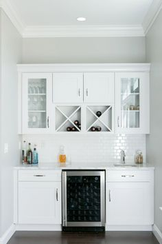 White, window-front cabinets create a bigger feel in this custom wet bar. #bardecorforhome