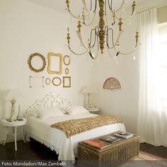 Alles andere als bescheiden: Für einen fürstlichen Schlaf sorgen der edle Kronleuchter und die Bilderrahmen in Gold. Das Bett mit Spitzenbettdecke und arabeskem…