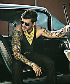 Homem tatuado com todos os estilos possíveis de tatuagens masculinas, das mais coloridas às em preto e branco.