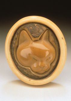 Japan  Cat, 20th century  Netsuke, Corozo nut, ivory; manju type. LACMA