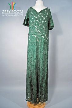 A full-length, v-neck, tube-style dress made of dark green lace. The pattern of the lace is of large peonies and stylized leaves. The dress would have been worn with a matching belt (not pictured). Grey Roots Museum & Archives Collection.