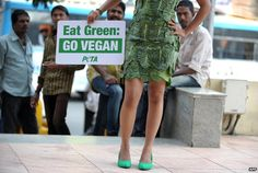 """A PETA activist in India holds a sign reading """"Eat Green: Go vegan"""""""