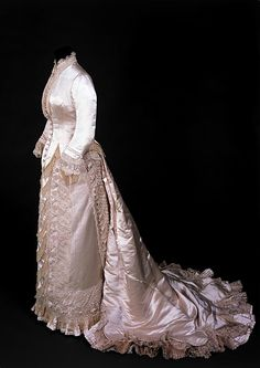 Wedding dress  Place of origin:  Paris, France (made)   London, England (worn)  Date:  1879-1880 (made)   19/02/1880 (worn)  Artist/Maker:  Charles Frederick Worth, born 1825 - died 1895 (designer)  Materials and Techniques:  Silk satin, lace and net, lined with silk, imitation of pearls embroidery, velvet  Museum number:  T.62 to B-1976  V