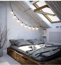 Attic in a barn feel. slanted ceiling, italian lights, dark wood baseboard with storage, sky light, wood paneling, secret book storage, gray, grey, white wash, whitewash,