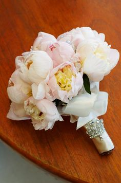The bride's bouquet, made up of pink and white peonies studded with crystals, is wrapped in champagne ribbon and a crystal cuff.