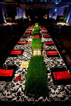 black, red and white reception. Wheat grass centerpiece, damask tablecloths and red napkins.