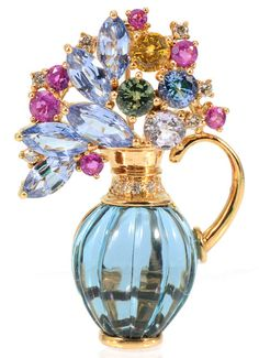 18K TOPAZ, DIAMOND AND SAPPHIRE FIGURAL BROOCH / PENDANT: 18k yellow gold pin in the form of a flower filled urn. The body is a fluted cabochon cut urn shaped London blue topaz. 11 Diamonds total approx. .12 Ct. The 10 round shaped and 5 marquise shaped sapphires total approx. 4.5 Ct. The sapphires are yellow, violet blue, green and purplish red. Stamped 750 and hallmarked with a W enclosed in a circle.
