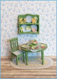 """1/4"""" Mayblossom Part Trois This 1/4"""" scale kit coordinates with our original holiday vignette kit and the part deux kit. INCLUDES: the table, a chair, the wall shelf, utensils, fabric tablecloth, flowers, butterdish & bowl, plates, postcards, napkins, the rug and all the artwork. Finished Size: Table approx 1"""" w x 3/4"""" d x 5/8"""" h. Chair approx 1/2"""" w x 1"""" h. Wall shelf approx 3/4"""" w x 3/16"""" d x 5/8"""" h."""