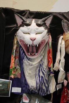 A fantastic cat mask carved in a traditional mask-making style.
