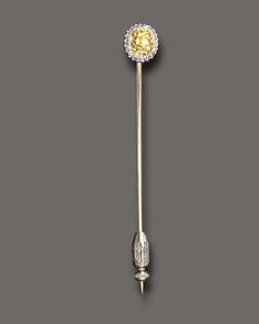 AN EXQUISITE ANTIQUE FANCY YELLOW DIAMOND AND DIAMOND STICK PIN   Set with an old mine-cut yellow diamond, within a single-cut diamond surround, mounted in 18k gold, circa 1900, with French assay mark