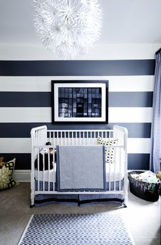 Bold stripes offer a unique blend of playfulness and sophistication in this nursery, which follows a strict blue-and-white color scheme. A skirt for the crib, patterned curtains and an eye-grabbing rug add softness to the space, while a grand flower chandelier proves that florals are for everyone.  Via Meredith Heron Interiors