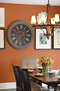 Thanks to the bold burnt orange tone of the Copper Mountain Sherwin-Williams paint, this collage of framed art in a variety of sizes creates unique visual interest in the breakfast room.