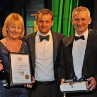 Property Care Association CEO Steve Hodgson (center), flanked by Julie and Bryan Hindle, receiving the PCA award for training and staff development 2013 on behalf of Brick-Tie Limited