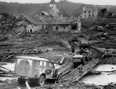 A U.S. convoy, including two ambulance crosses a temporary bridge in the Moselle. Photo taken at the third court offensive in the region of Koblenz, Germany in March 1945.