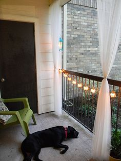Great balcony decorations. Love the lights and curtains! I would just hang the lights from the top though.