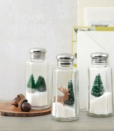 """Here's one Yuletide idea that's definitely worth its salt: Turn under-a-dollar shakers into mini winter wonderlands by nesting toy evergreens and deer atop iodized """"drifts.""""   - CountryLiving.com"""