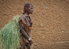 Eric Lafforgue  www.ericlafforgue.com Hamer woman Carrying A Load Of Straw Wearing Skin Device Omo Valley Ethiopia