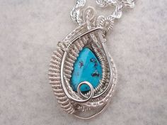 """Mini Blue Turquoise Heady Wire Wrapped Pendant Necklace. Lovely genuine turquoise cabachon. Pendant measures 1 3/4"""" Designed and hand wrapped by me in silver plated silver enameled copper wire."""