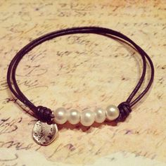 Freshwater pearls & leather bracelet with silver charm & sliding closure   . . ....