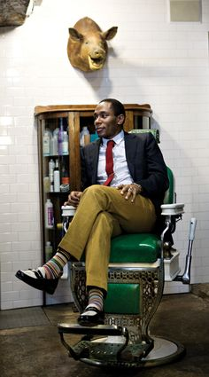 Yasiin Bey in Chartreuse pants, striped socks, black and white oxfords, pale blue shirt, and an ox blood tie.