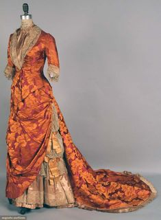 PURPLE & ORANGE SILK BUSTLE GOWN, 1878-1883 2-piece silk brocade, purple w/ orange flowers & foliage, long fitted bodice, trimmed w/ taupe satin & lace; draped skirt front, very long train. BMCC