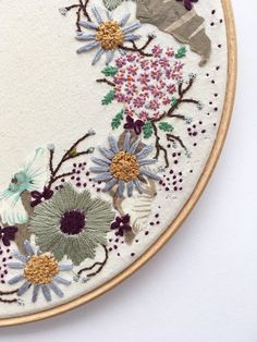 Floral Ring is a handmade piece. Hand embroidered using cotton and silver embroidery threads, with added fabric appliques for a more intricate and unique design. Framed with a wooden embroidery hoop size 9. Can be hung on the wall with or without the ribbon or for a more flexible style it can be left leaning on a shelf... Only one available and ready for shipping! The packaging consists of an envelope with cardboard backing inside. Please get in touch for similar orders ( note: will need...