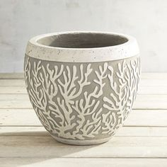 Intricately detailed, our embossed planter is handcrafted of cement in natural shades of gray and ivory.This pot features a stylized design that adds texture and visual interest indoors or out.