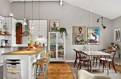 kuchnia z jadalnią z plakatami i fotografiami na ścianie, biała gablotą,oldchoolpwymi krzesłami,drobnymi meblami vintage i z industrialnymi lampami