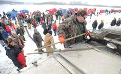 People watch as fish are released by the DNR at Ada Hayden Park on Saturday, Feb. 6. Photo by Nirmalendu Majumdar/Ames Tribune  http://amestrib.com/news/anglers-break-ice-search-trout-ada-hayden-lake