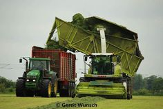 #Farming: A Claas Jaguar forager dumps its load to an awaiting tipper pulled by a John Deere tractor.