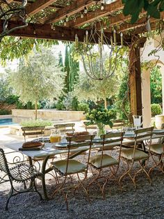 This outdoor dining area designed by Tara Shaw is an oasis with wisteria arbor, vintage tables and chairs, iron chandelier and pea gravel.