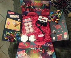21st birthday care package for my sailor! It includes: 2 jars of cake, a jar of icing, 2 shot glasses, a flask, beer pong balls, a birthday button, a hangover kit, a deck of cards, and also has a Barcelona jersey and he World Cup sticker album.