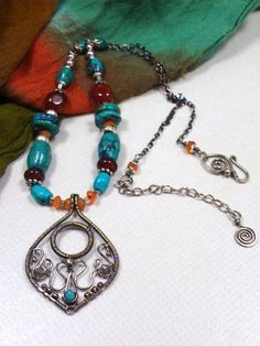 A charming artisan necklace, with a bit of Oriental flair, completely handmade and unique. It all started with the wire wrapped pendant, which I chose to oxidize and decorate with a tiny Sleeping Beauty turquoise bead and two sparkly Labradorite beads. Then I created a string of