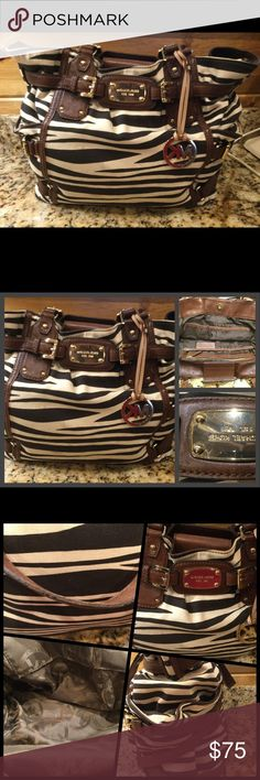 Authentic Michael Kors Brown Leather/Fabric Purse Authentic preowned Michael Kors med to large shoulder straps purse. It comes with the long shoulder strap. The metal MK placket on the purse has some scratcher. The fabric of the body, interior and bottom of the purse show little signs of wear. The leather handles do have some patina and fraying. Please see pictures. The size of the bag is large. From a smoke free home with pets. No holds, trades or off site transactions. Use offer button to…