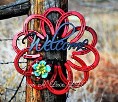****This beautiful horseshoe wreath is painted . It is adorned with a galvanized welcome and metal flower or bow. Item is made from all new horseshoes. Welcome is attached with magnets as well as the flower