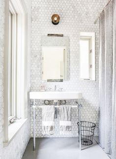White bathroom tiled with hand towels and single industrial light above mirror