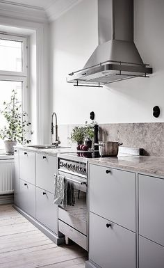 A Scandinavian kitchen with black touches, a stone backsplash and counters looks ethereal